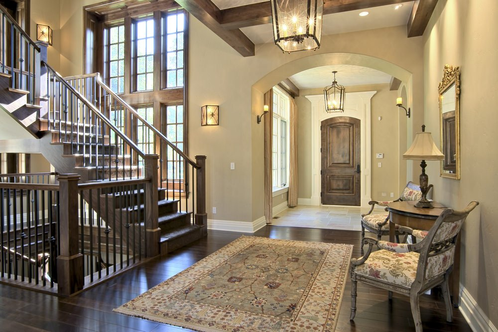 This foyer features a spiral staircase with wooden steps and iron railings. The flooring is topped by a classy rug and there's a set of beautiful chairs on the side.