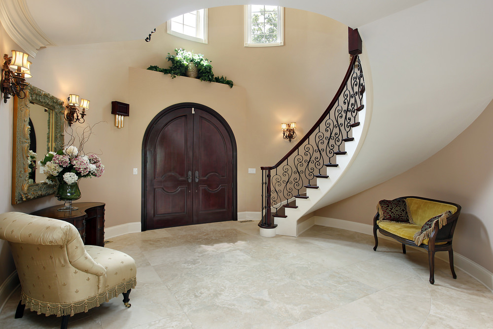 This foyer lighted by gorgeous wall lighting features a high ceiling and a gorgeous staircase. The chair on the side looks absolutely lovely.