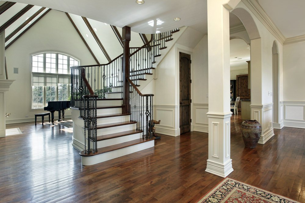 A classy foyer featuring hardwood flooring and white walls with a high towering ceiling.