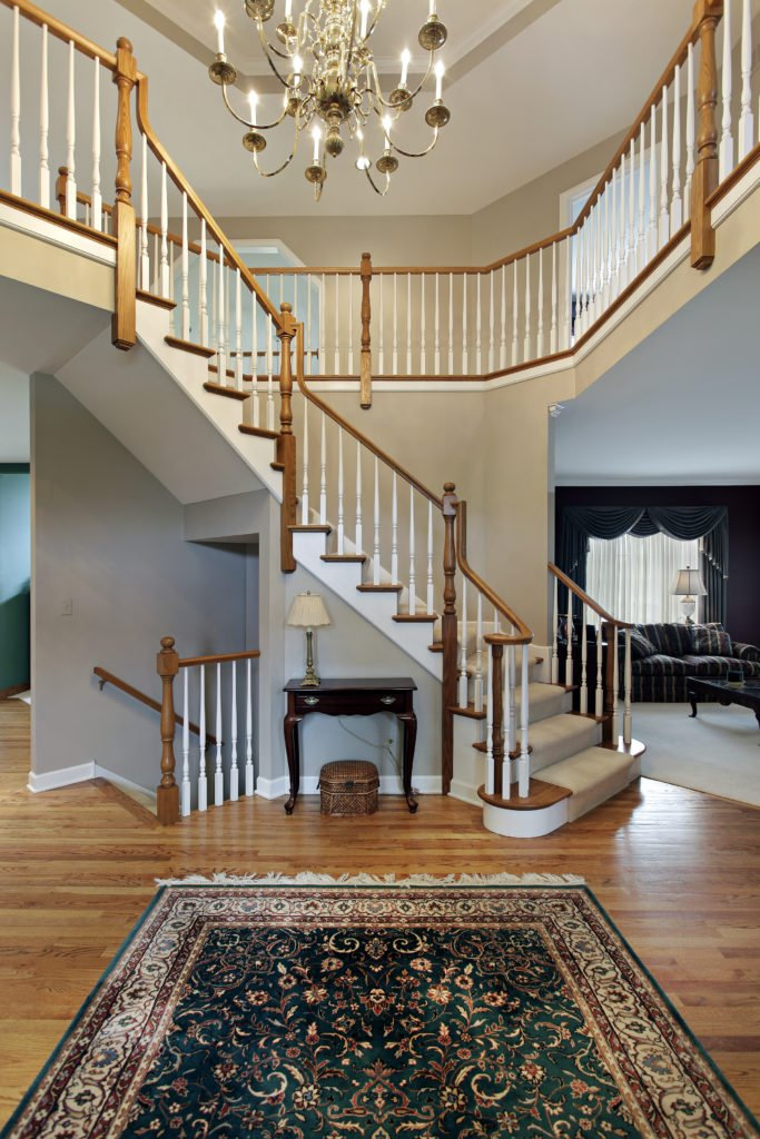 This home boasts an amazing landing featuring an elegant rug and a stunning staircase covered with white carpet floors.