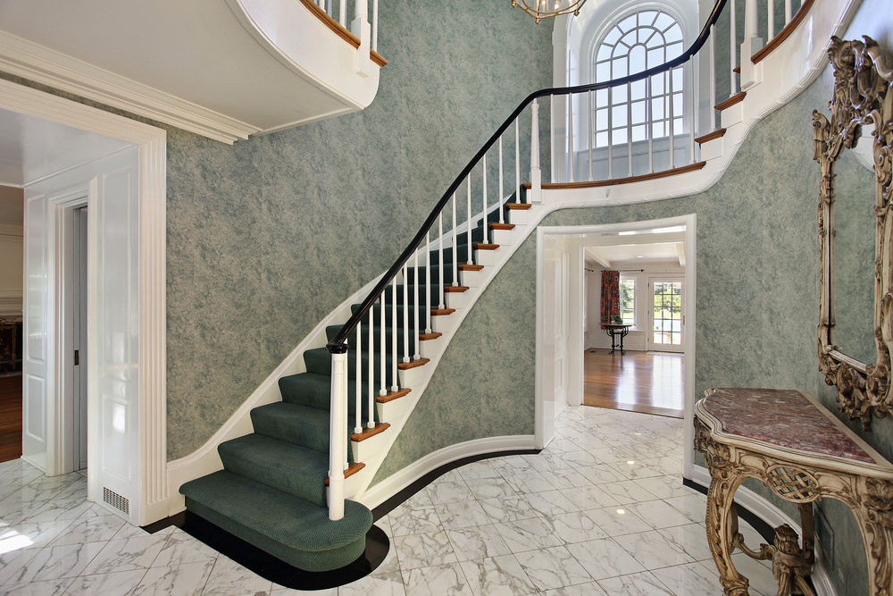 This home boasts a beautiful foyer featuring green classy walls and green carpet staircase steps along with a gorgeous chandelier lighting.