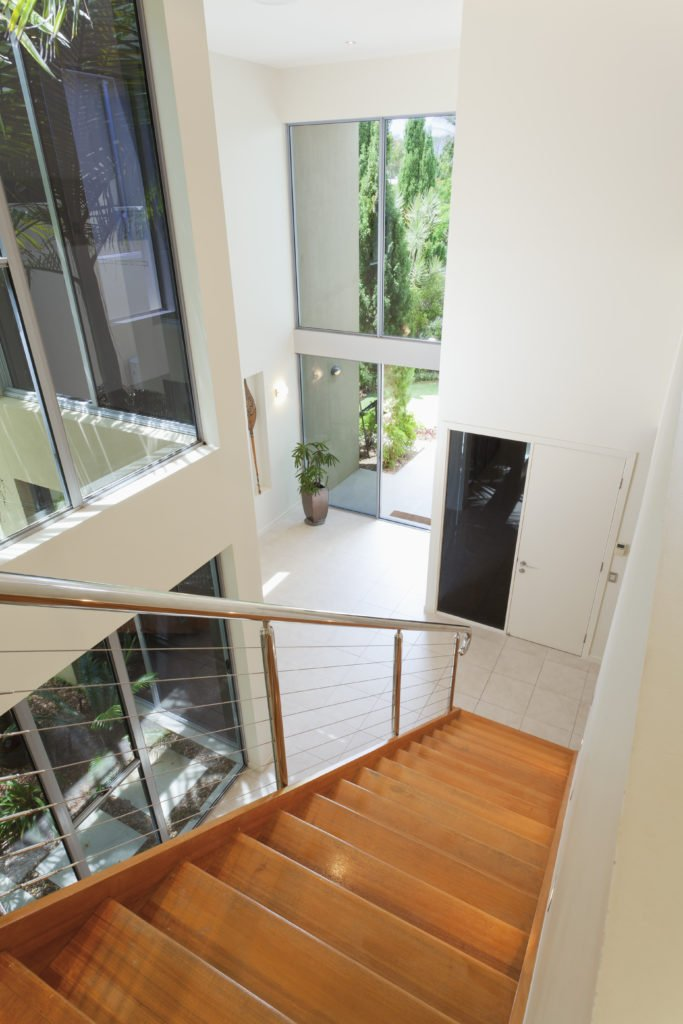 A top view of the wooden staircase with stainless steel railing in this white foyer surrounded with glass windows.