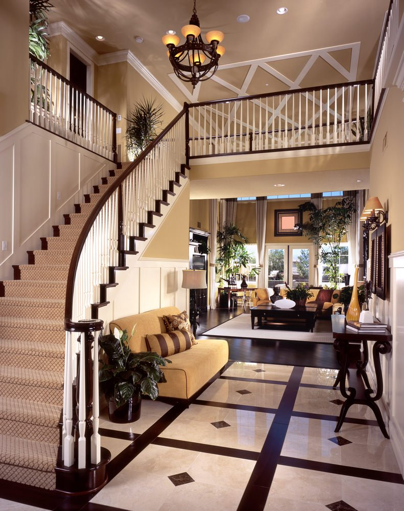 This elegant foyer features a stylish and sparkling flooring along with a classy couch.
