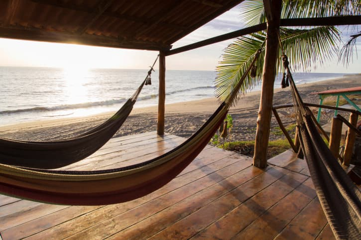 Sea-side covered deck with hammocks all over the place.