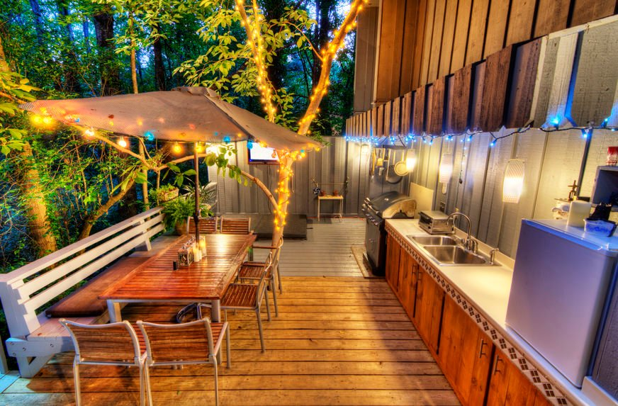 This deck features a complete set of outdoor kitchen and dining lighted by a romantic lights and surrounded by beautiful greens.