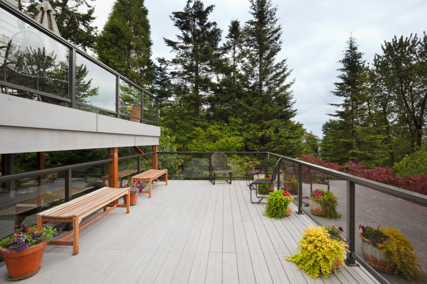 This deck offers a large space. Bench seats and comfortable chairs on both sides along with colorful plants.