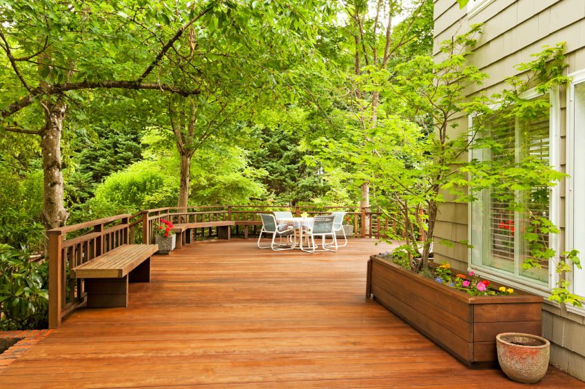 This deck features bench seats and a white small dining table set. The deck is surrounded by magnificent greenery.