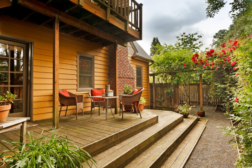 Small deck featuring a small coffee table set. This deck is sorrounded by colorful plants and beautiful greens.