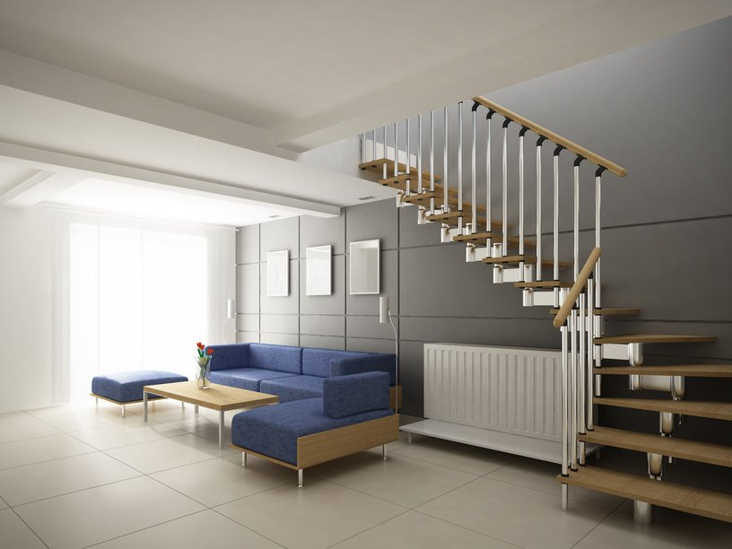 A living space under a staircase with white railings, single stringer and wood tread on a beautiful dark gray wall.