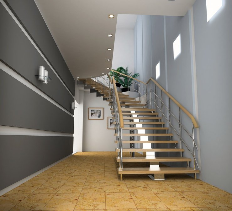 Modern hallway lined with gray paneled walls and illuminated by sconces and recessed ceiling lights. It includes a mono stringer staircase with wood treads and steel railings fixed to the light blue wall.