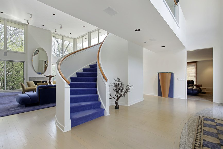 Entryway showcases a white curved staircase covered with blue carpet and lined by wooden handrails.