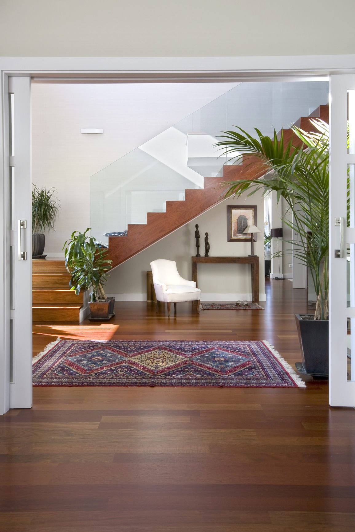 This foyer features a hardwood flooring and white walls. The white chair looks charming.