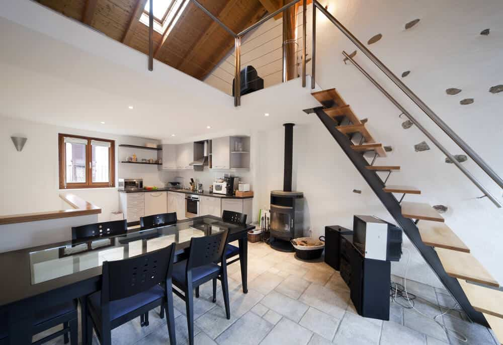An eat-in kitchen showcasing a stone tile flooring and white wall fitted with a fireplace and an open riser staircase with single stringer and aluminum handrail.