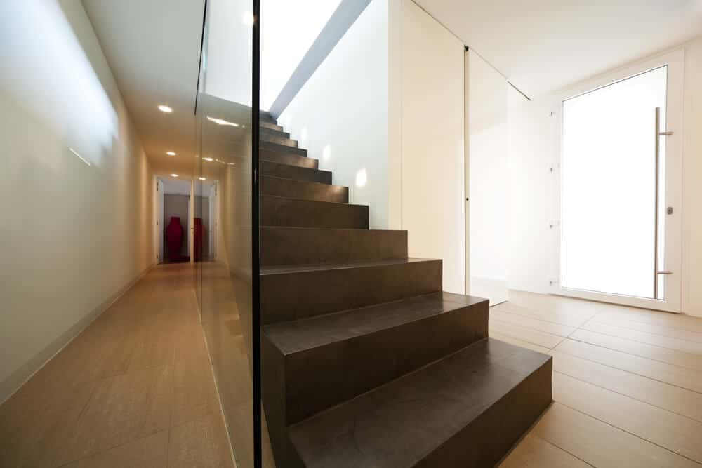 Long and narrow hallway with a concrete straight staircase fixed with glass railing and illuminated by stair lights.