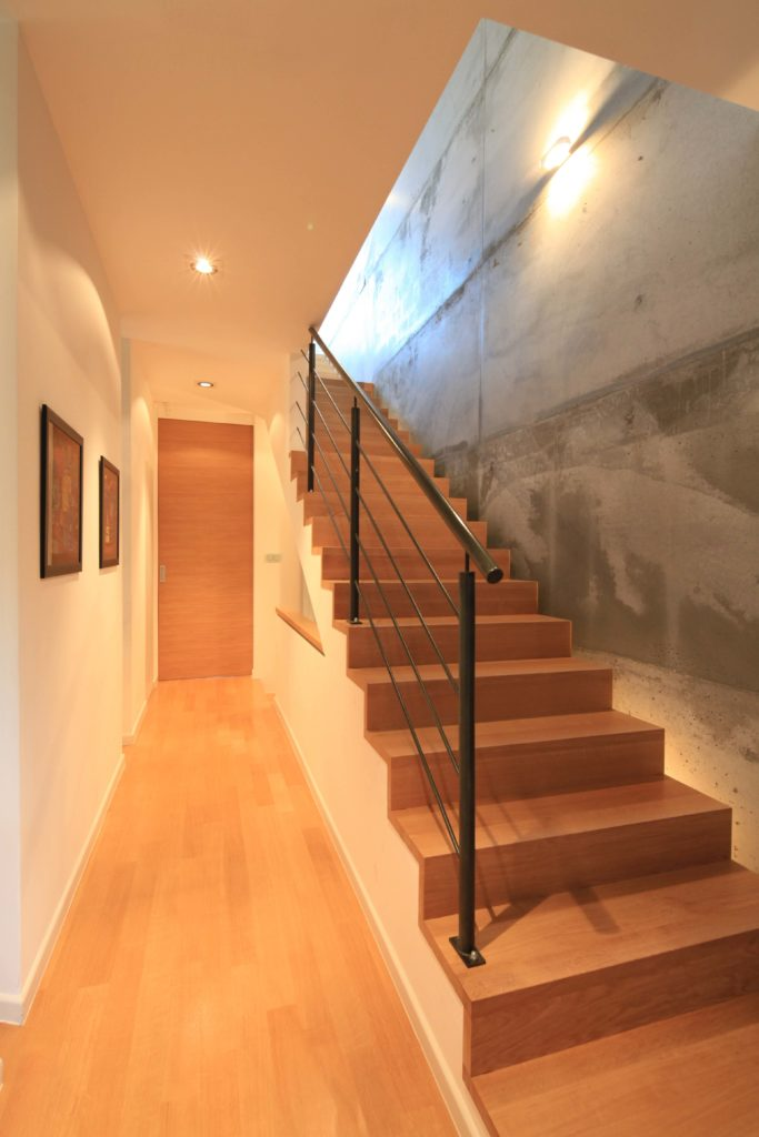 Bright hallway boasts white walls and hardwood flooring that complements with the staircase fitted with black railing.