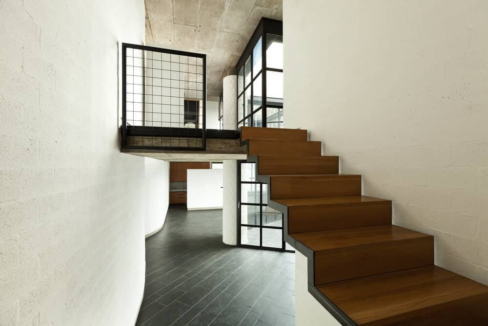 Wooden staircase without railing lined with black stringer and fixed to the white brick wall.