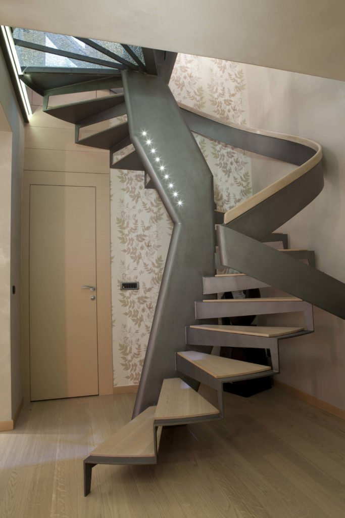 A unique staircase with light wooden treads that match the hardwood floor and without stringer creating a floating look. It has stylish gray handrails accented with led lights.