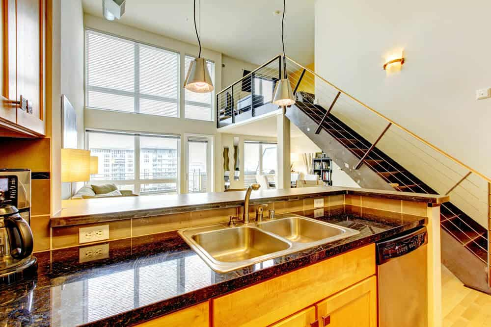 Warm kitchen with a straight staircase fitted with concrete stringer and thin steel railing topped with wooden handrail.