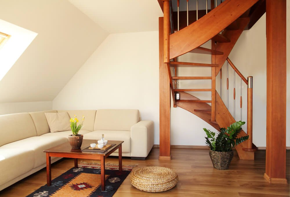 A white living room under a sloped ceiling. It has a center table that matches the wooden staircase with metal spindles and complements the hardwood flooring.