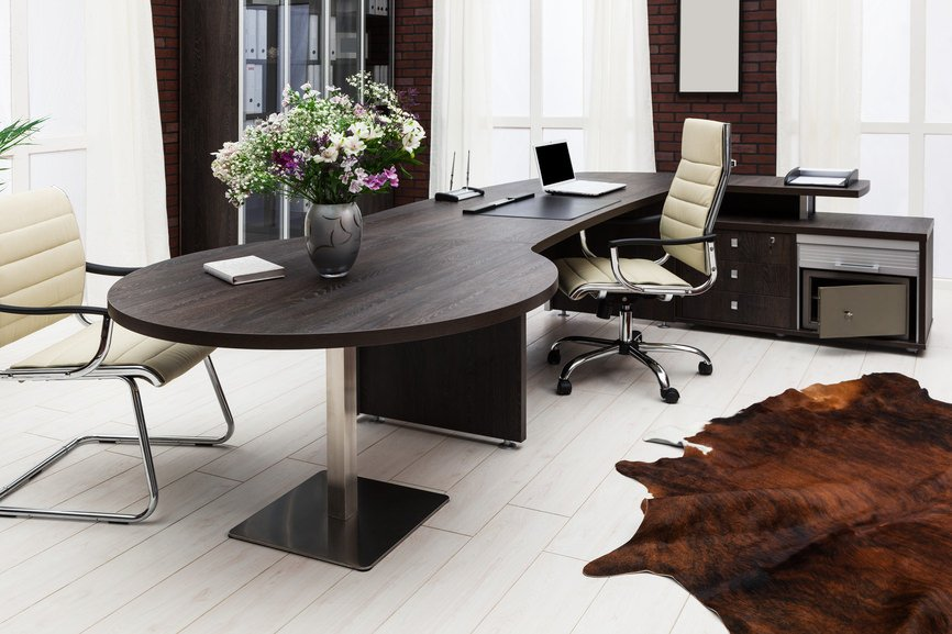 Modern home office with a dark wood L-shaped desk fitted with a round table that's topped with a flower vase on its end. It has brick walls and a cowhide rug that lays on the wood plank flooring.