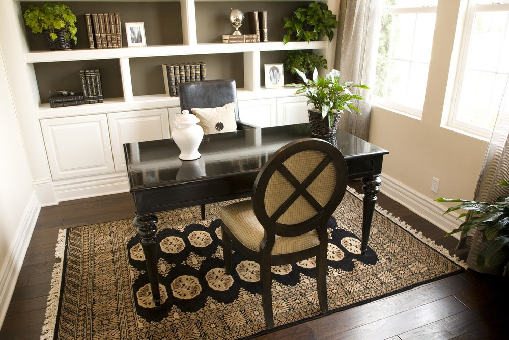 It may be a small room, but this office is definitely the executive style with built-in white shelves, gorgeous dark wood desk with guest chair. The room has new hardwood floors with a well-selected area rug that ties the room together.
