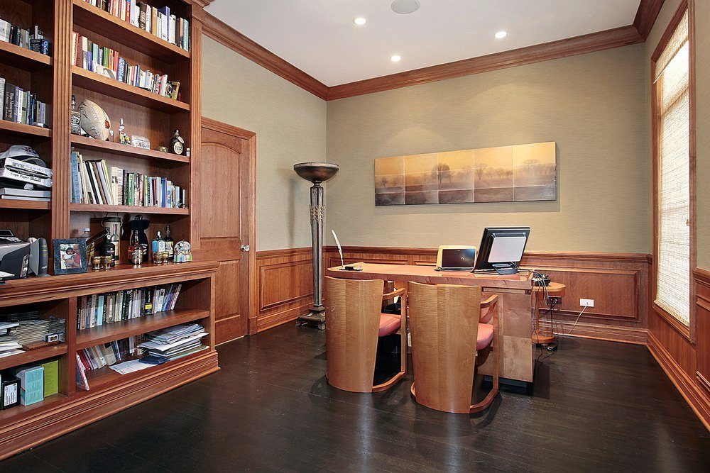 A classic home office decorated with multi panel canvas wall art mounted above the wooden wainscoting. It has a wooden office desk and chairs fitted with red cushions.