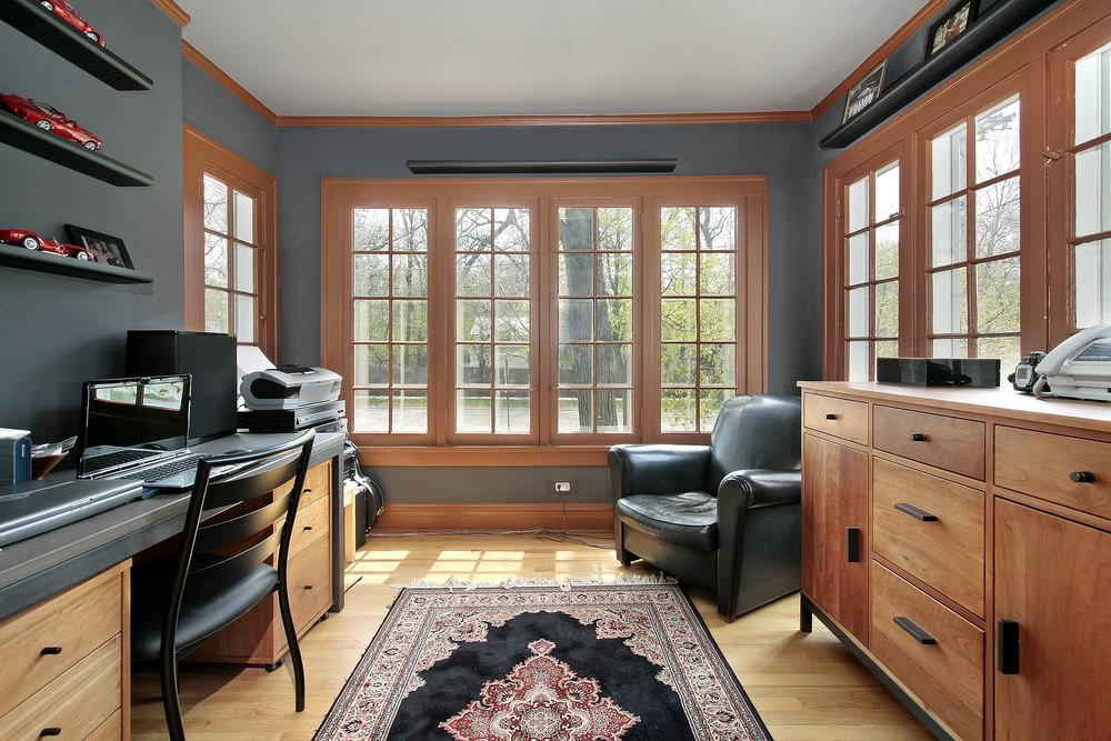 Fresh home office with gray walls fitted with wooden framed windows and black floating shelves. It has a wooden drawer and desk paired with black chairs over light hardwood flooring topped by a vintage rug.