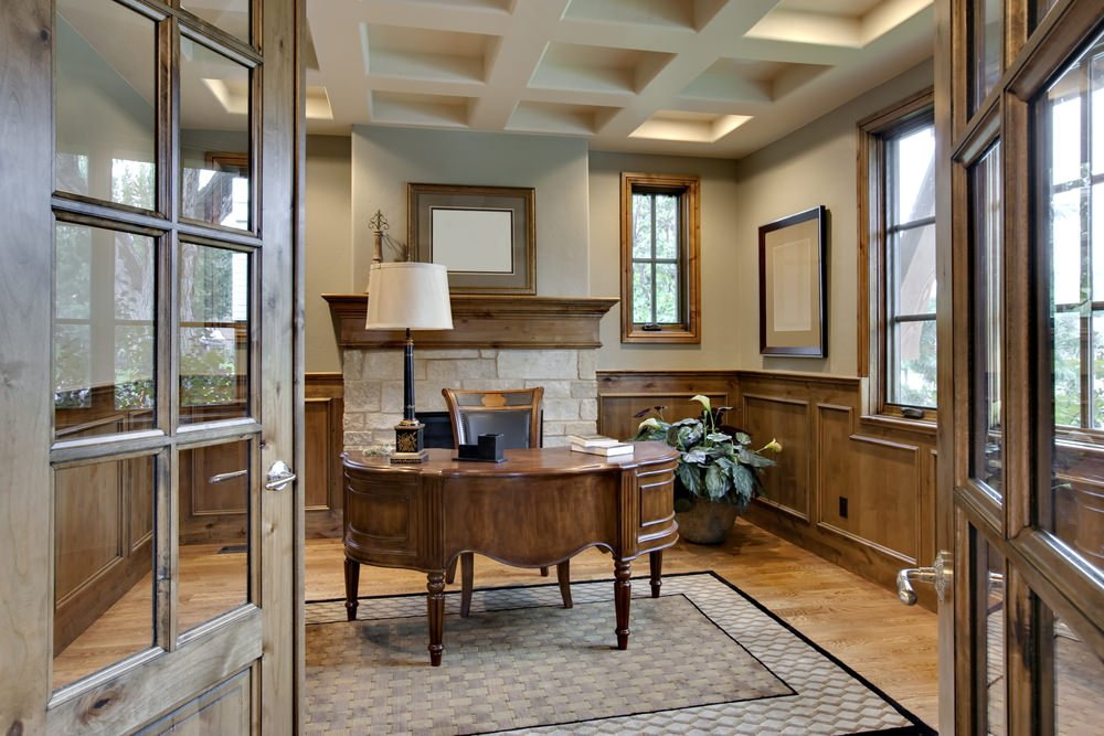 An elegant home office with a classic office desk and chair with a fireplace set on the back. The room has a stunning coffered ceiling.