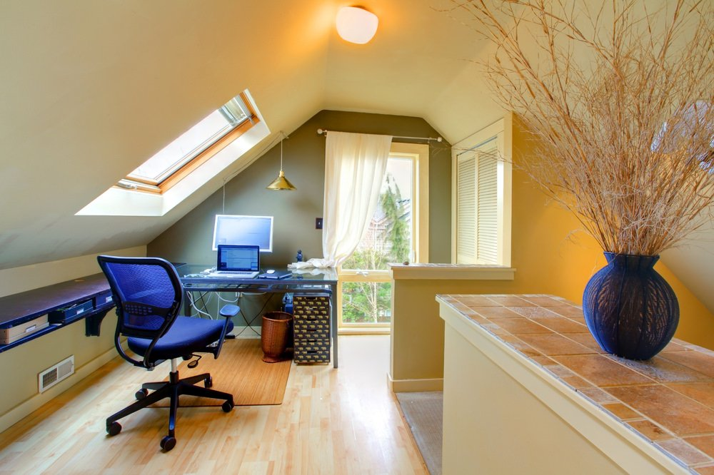 This home office features a stylish desk set up. The room features hardwood flooring and charming windows.