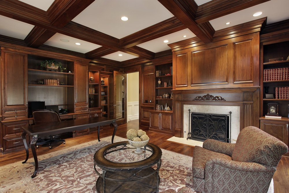 This home office offers a large fireplace and multiple bookshelves, along with a large rug covering the hardwood flooring.