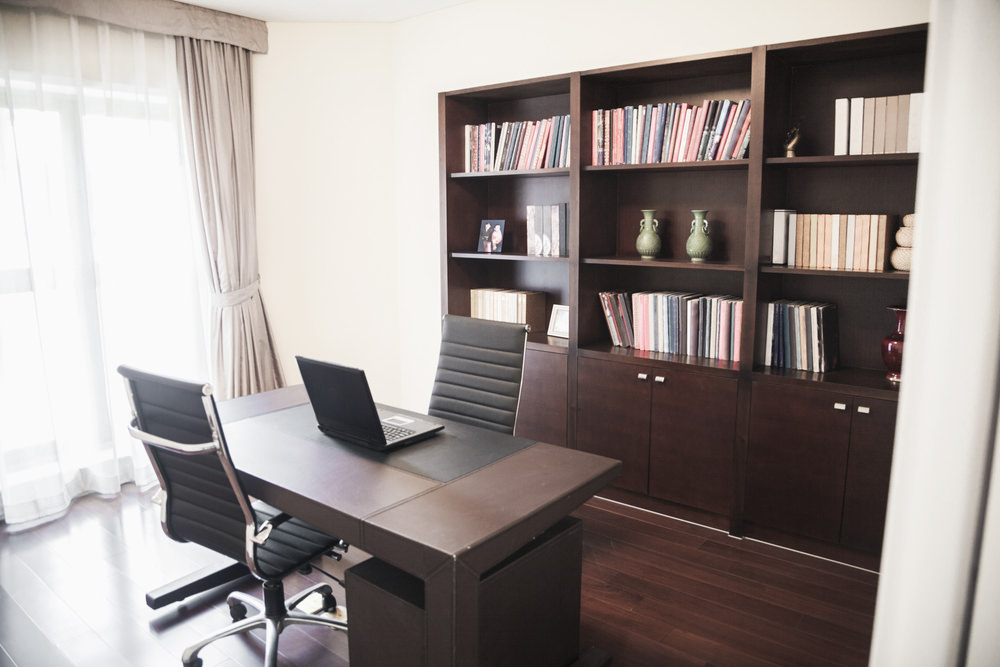 This home office offers matching black chairs facing each other with a dark wood desk in between which complements with the bookshelf.
