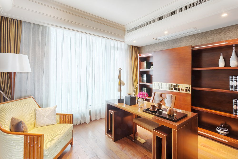 Classy home office showcases a cream lounge chair lighted by a floor lamp and faces the stylish desk and open shelving lined with a sliding wooden panel.