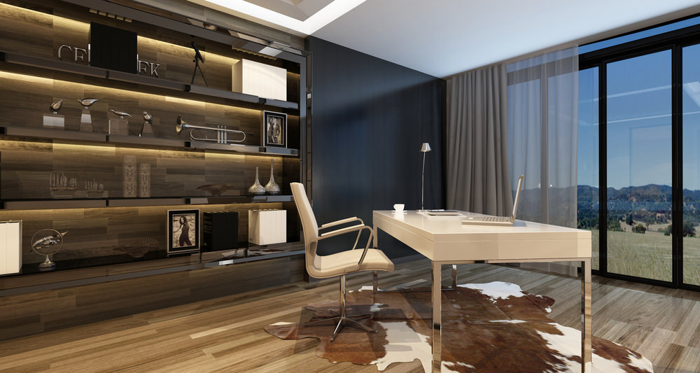 Sophisticated home office with built-in display cabinet and floor to ceiling glass windows covered in gray and sheer curtains. It has a smooth white desk and sleek chair that sit on a cowhide rug.