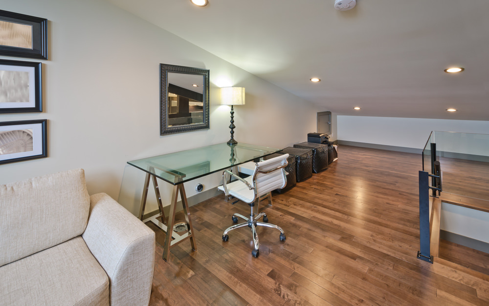 Expansive home office furnished with a gray sofa along with white leather office chair and glass top desk with a table lamp. It has wood plank flooring and shed ceiling fitted with recessed lighting.
