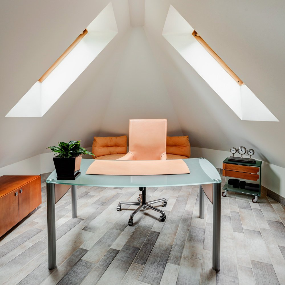 I love this modern attic home office with two skylights and small glass-topped modern desk. It's a beautiful space where it's removed from the rest of the home for privacy and quiet.