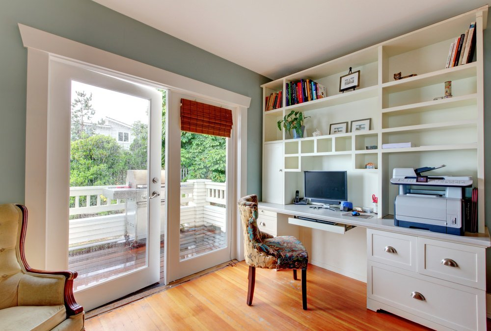 A corner home office boasts a gorgeous wingback chair and immense white desk with open shelving over hardwood flooring.
