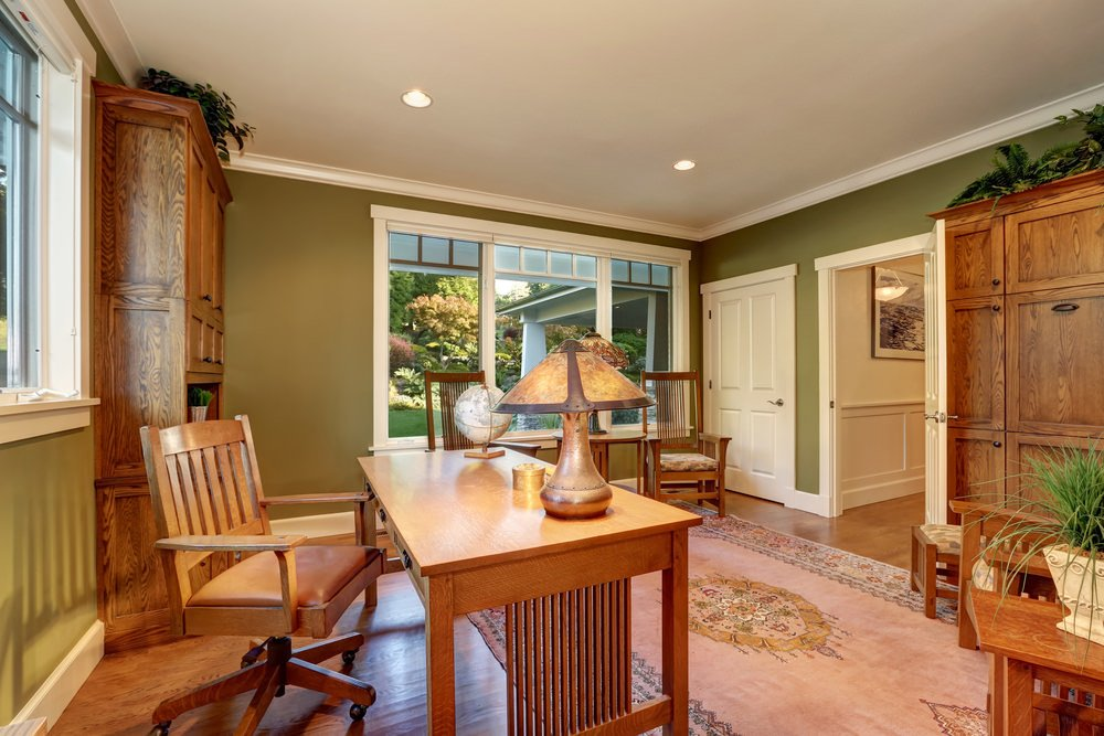Cozy home office with moss green walls fixed with wooden built-in storages and glass paneled windows. It has a wooden chair and smooth desk topped with a globe and table lamp.