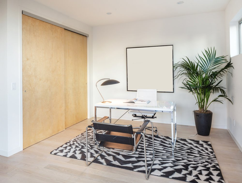 Minimalist home office offers solid wood sliding doors and whiteboard across the white desk paired with a black metal chair over a striking black rug.