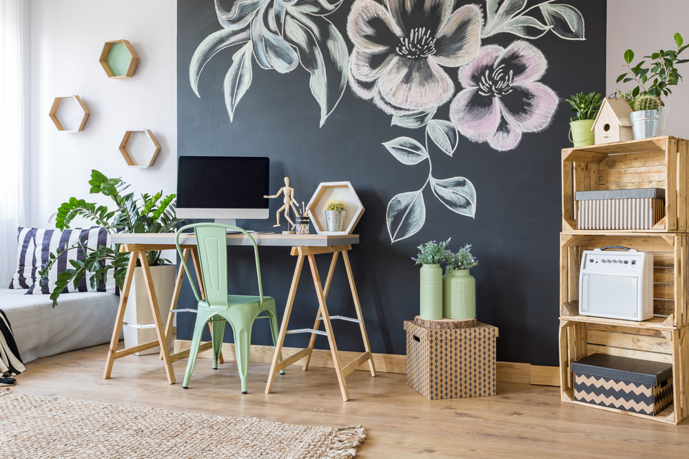 Fresh home office designed with black floral wall art and hexagonal wooden shelves mounted on the white wall. It has a light wood desk and green chair along with rustic open shelves filled with storage boxes.