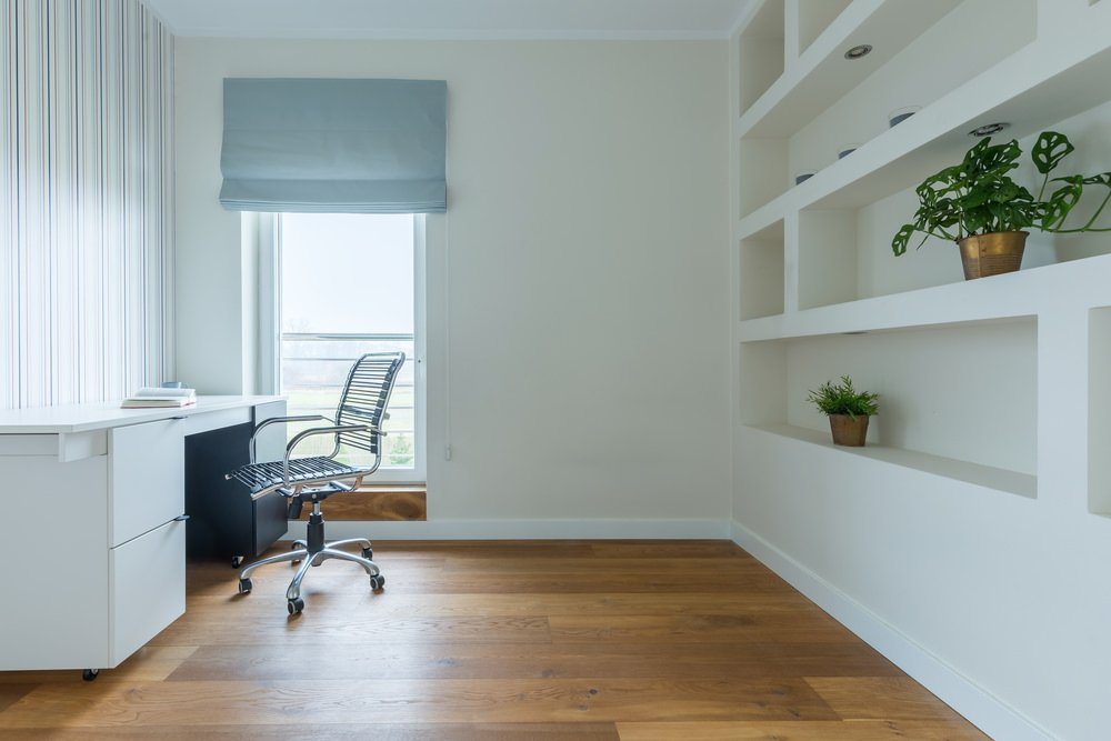 White home office features built-in open shelving decorated with greenery. It includes a striped accent wall and glass window covered in a light blue roman shade.