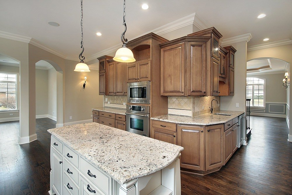 This kitchen offers a white center island and brown kitchen counters with white granite countertops. The home also has hardwood floors.