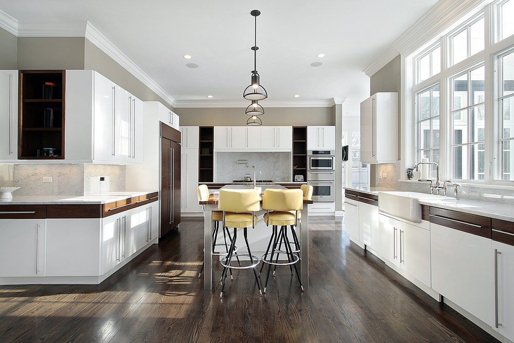Large industrial kitchen featuring hardwood flooring and a beautiful set of ceiling lights. The center island provides space for a breakfast bar.