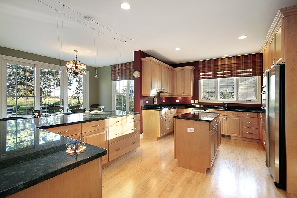 Spacious kitchen features walls painted deep red, wood kitchen cabinets with black marble countertop, an island kitchen bar, tiny pendant lights and stainless steel appliances.