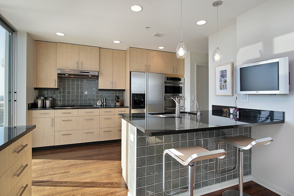 Attractive gray tile backsplash and breakfast island with black granite countertop accent the wood kitchen cabinets and hardwood flooring. A pair of modern kitchen bar stools complement the glass pendant lights.Attractive gray tile backsplash and breakfast island with black granite countertop accent the wood kitchen cabinets and hardwood flooring. A pair of modern kitchen bar stools complement the glass pendant lights.