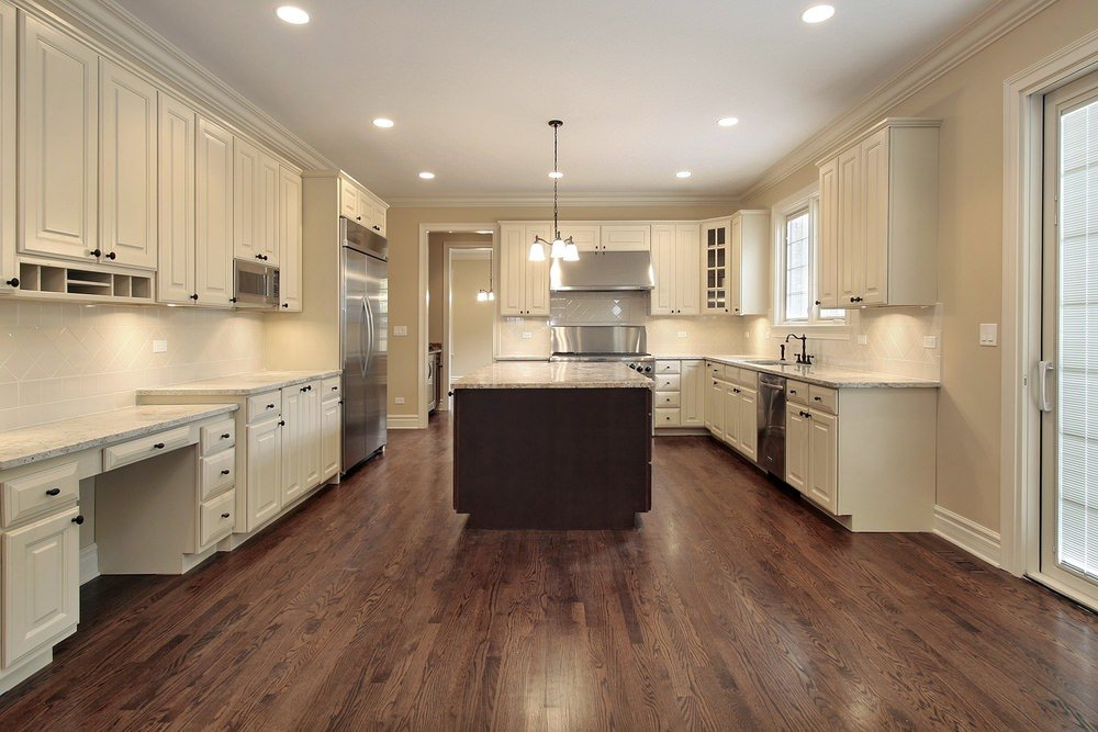 Large kitchen featuring hardwood floors and white cabinetry, along with beige walls, recessed ceiling lights and a gorgeous pendant lighting.