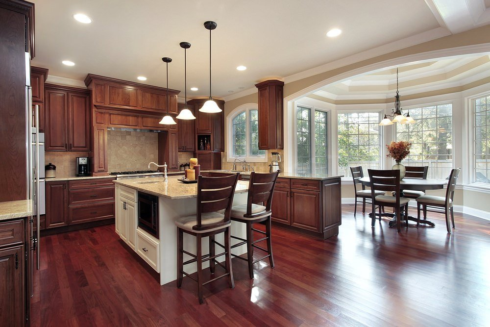 Elegant kitchen features dark wood cabinet, brick tile backsplash and three pendant lights hung over a white breakfast island with gray marble countertop and two wooden with cushion counter stools.