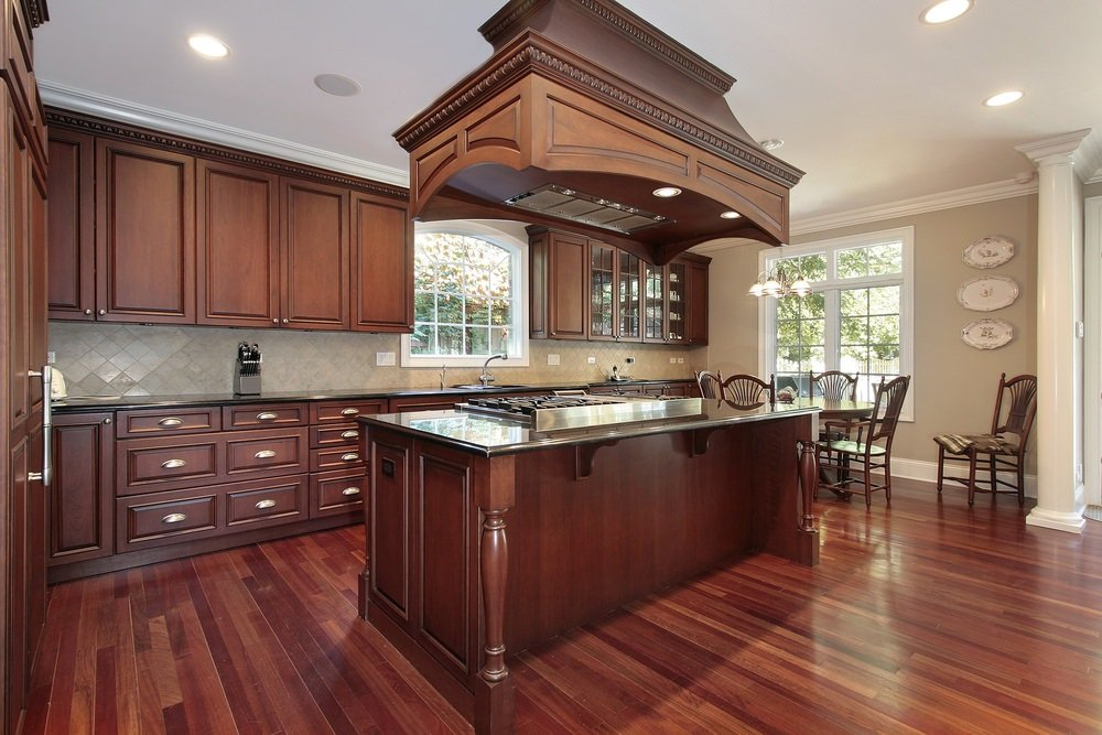 A gorgeous wood range hood is fixed above a stainless steel cooktop built into the dark wood kitchen island. It harmonizes with the wood cabinets surrounding the diamond tile backsplash.