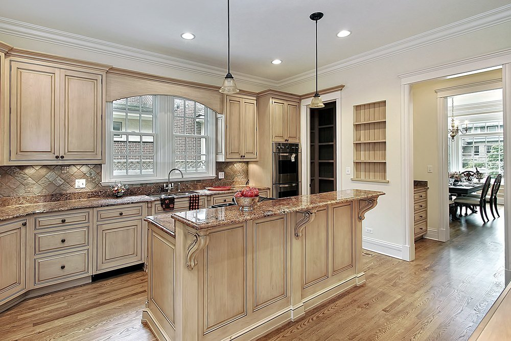 An elegant kitchen that uses natural wood tones on cabinets and floor complements brown marble countertops and white ceiling creates a unified look.
