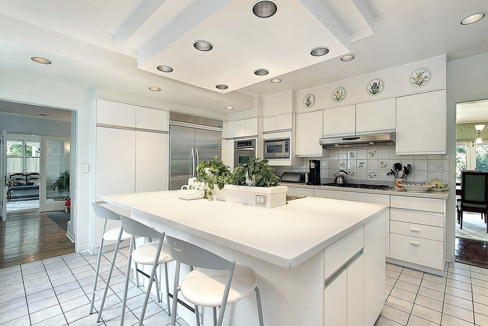 Sleek kitchen designed with floral plates that are mounted above the white cabinetry complementing with the backsplash tiles. It has a breakfast island with bar stools that sit on white tiled flooring.