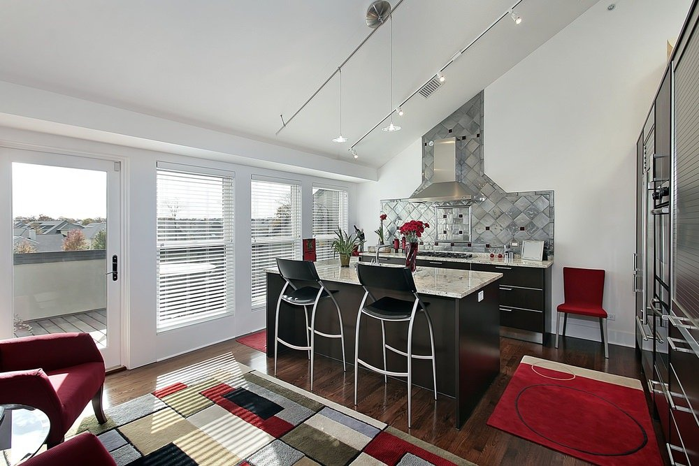 Glamorous kitchen with a subtle pop of color red from chairs, rugs and flowers. It features black cabinets with marble countertops, stainless steel range hood that stands over a beautiful gray tile backsplash and cooktop, and industrial lights on a sloped ceiling.